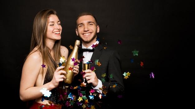 Feliz, homem mulher, com, garrafa, e, copos bebidas, entre, confetti Foto gratuita