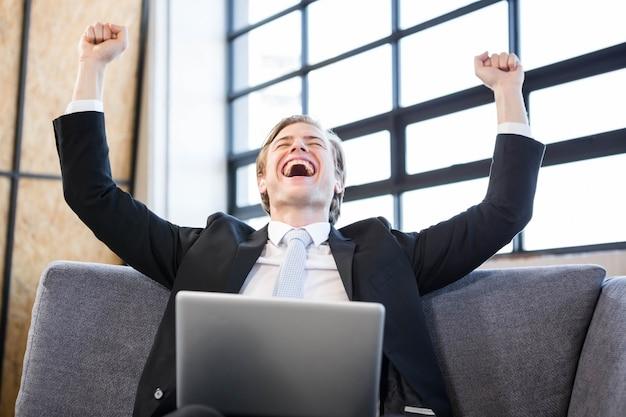 Feliz, homem negócios, levantamento, mãos, com, excitação, frente, laptop Foto Premium