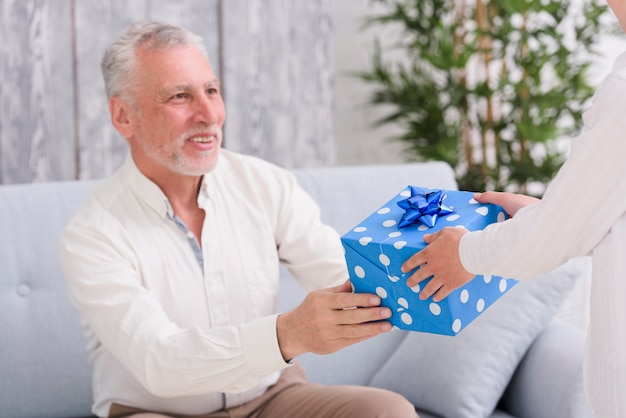 Feliz, homem sênior, sentando, ligado, sofá, recebendo, presente, frente, um, menino Foto gratuita