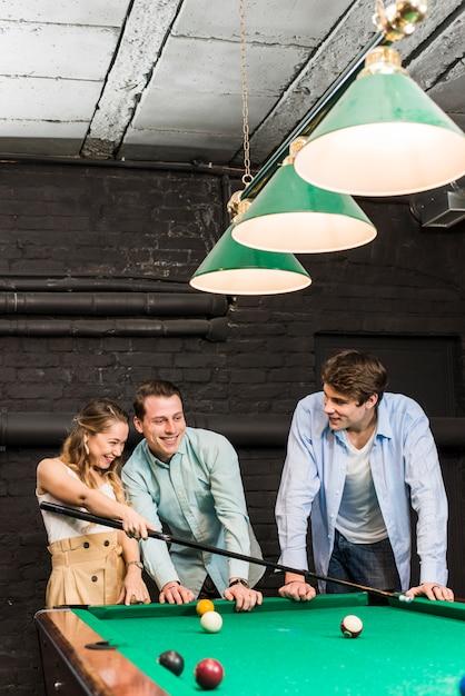 Feliz, homens jovens, e, mulher, jogando bilhar, em, clube Foto gratuita
