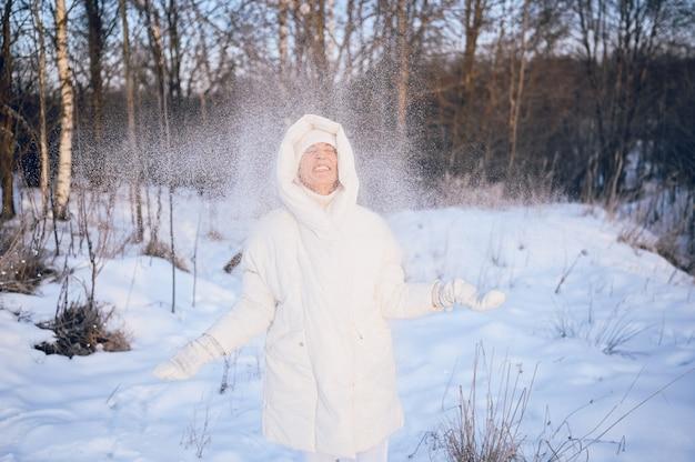 Feliz idosa sênior mulher madura em outwear quente branco brincando com neve no inverno ensolarado ao ar livre. Foto Premium