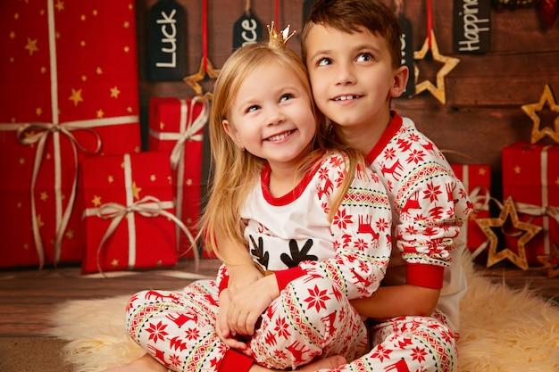 Feliz irmão e irmã de pijama de natal à espera de presentes na véspera de natal Foto Premium