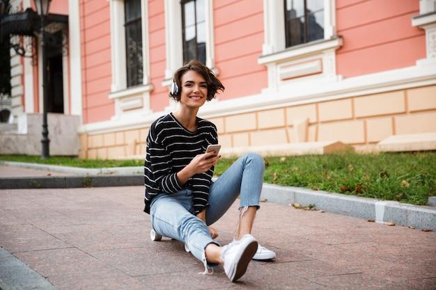 Feliz jovem adolescente com fones de ouvido Foto gratuita