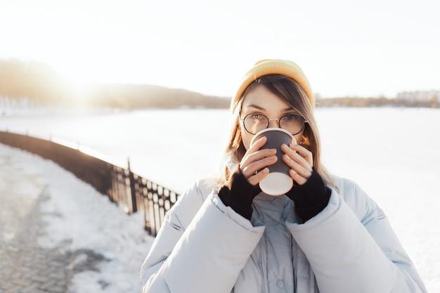 Feliz jovem adolescente segurando uma xícara de café para viagem Foto gratuita