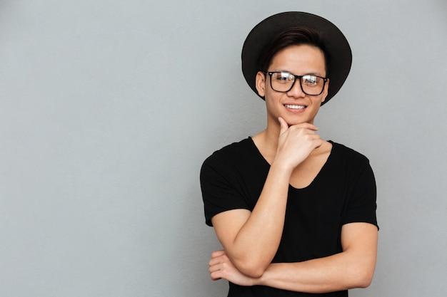 Feliz jovem asiático em pé isolado sobre parede cinza Foto gratuita