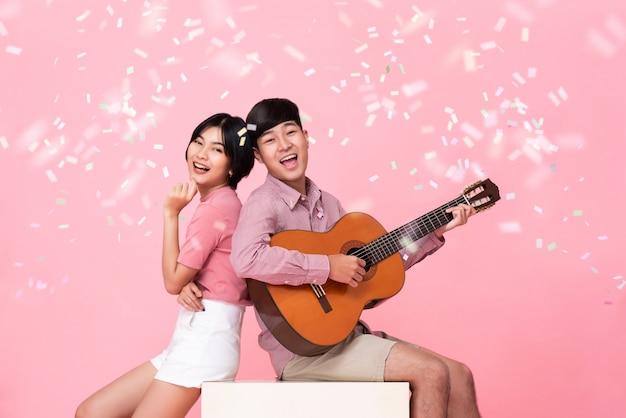 Feliz jovem asiático tocando violão e cantando com sua namorada Foto Premium