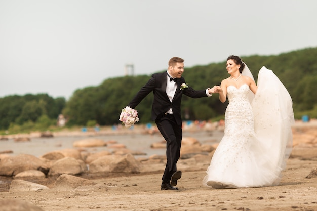 Feliz jovem casal de noivos se divertindo na praia Foto Premium