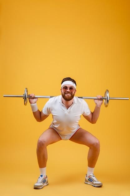 Feliz jovem desportista fazer exercícios de esporte com barra Foto gratuita