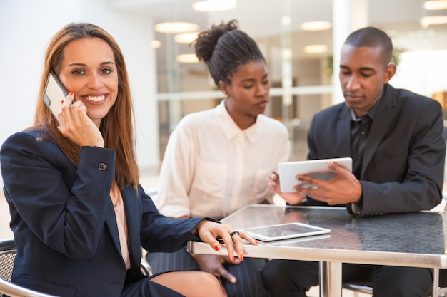 Feliz jovem empresária falando no celular no café Foto gratuita