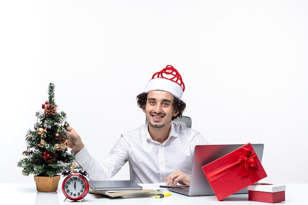 Feliz jovem empresário com chapéu de papai noel engraçado, decorando a árvore de natal e comemorando o natal no escritório em fundo branco Foto gratuita