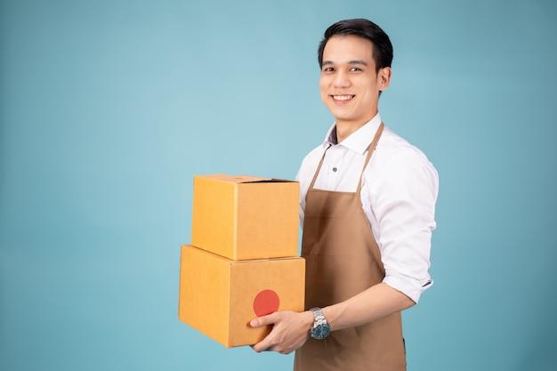 Feliz, jovem, entrega homem, ficar, com, encomenda postal, caixa Foto Premium