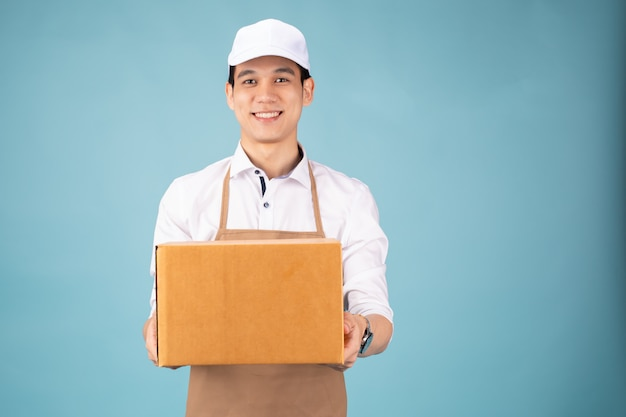 Feliz jovem entregador em pé de boné branco com caixa postal Foto Premium