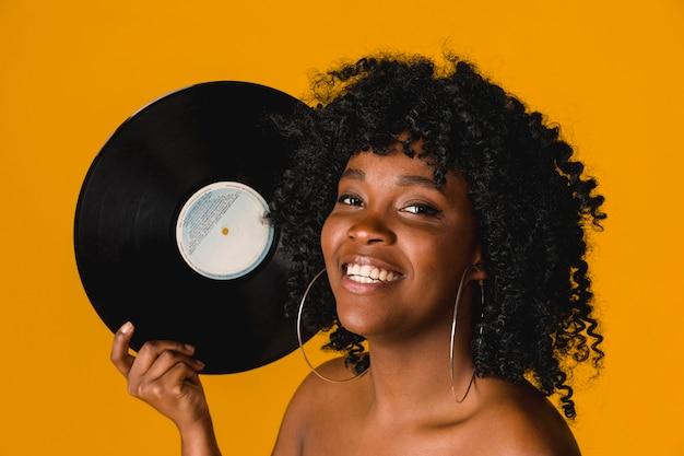 Feliz, jovem, étnico, mulher segura, prato vinil, ligado, fundo brilhante Foto gratuita