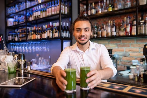 Feliz jovem garçom ou barman de camisa branca passando para você dois copos de smoothie de vegetais frescos com garrafas de álcool no fundo Foto Premium