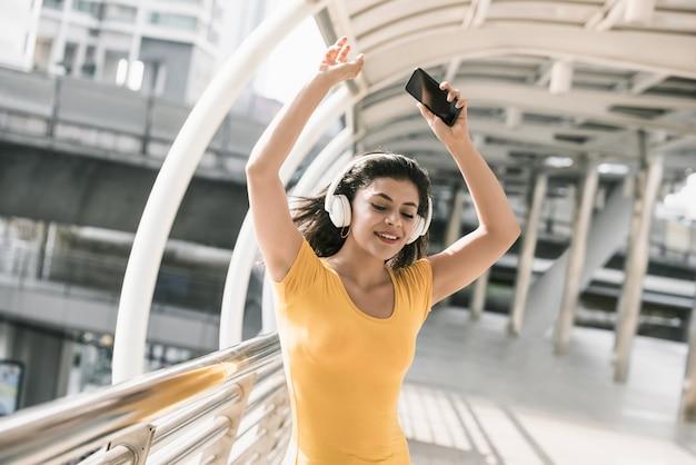 Feliz, jovem, latina, mulher, escutar música, de, fones Foto Premium