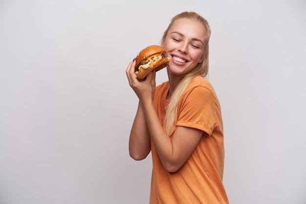 Feliz jovem loira de cabelos compridos com penteado casual, mantendo o saboroso hambúrguer fresco nas mãos e sorrindo alegremente com os olhos fechados, em pé contra um fundo branco Foto gratuita