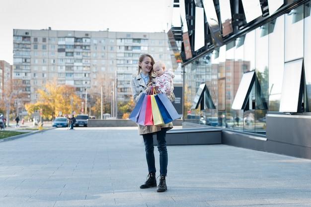 Feliz jovem mãe com filha nos braços e sacos de compras na mão. dia de compras. shopping na parede Foto Premium