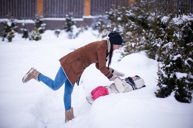 Feliz jovem mãe com sua filha pequena se divertindo no quintal em um dia de inverno Foto Premium