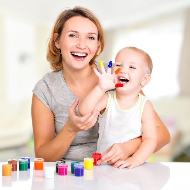 Feliz jovem mãe e filho com as mãos pintadas Foto gratuita