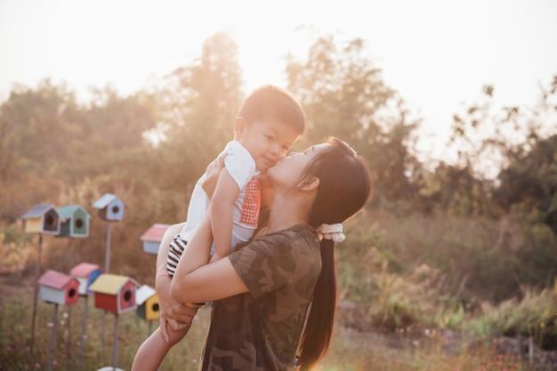 Feliz jovem mãe jogando e se divertindo com seu filho pequeno no parque em um dia ensolarado de verão Foto gratuita