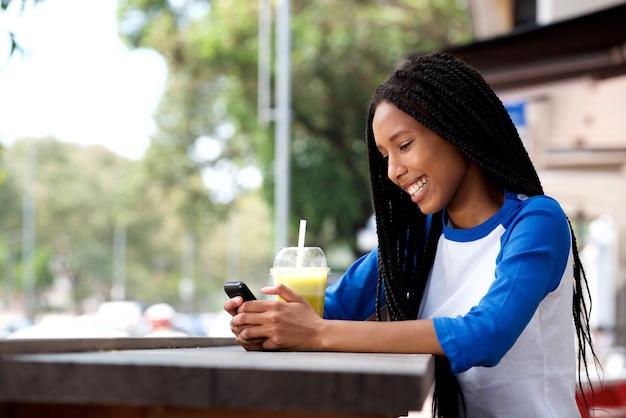 Feliz, jovem, mulher africana, sentando, em, café ao ar livre, usando, cellphone Foto Premium