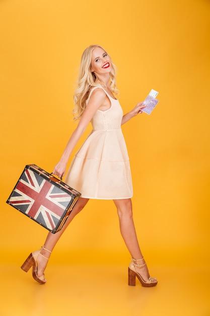 Feliz jovem mulher loira segurando a mala impressa do reino unido Foto gratuita