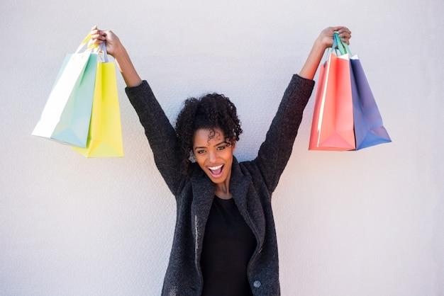 Feliz jovem negra com sacos de compras contra uma parede branca Foto Premium