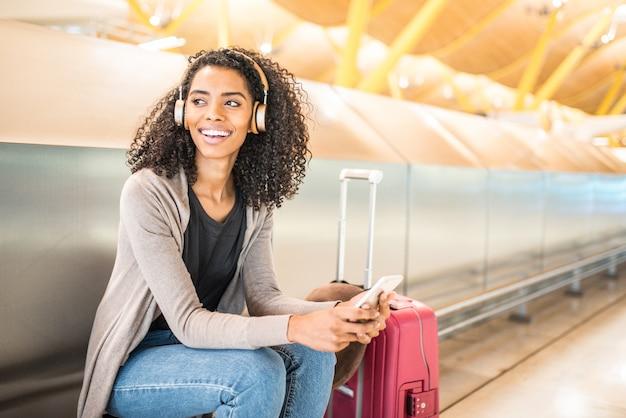 Feliz jovem negra ouvindo música com fones de ouvido e telefone móvel no aeroporto Foto Premium