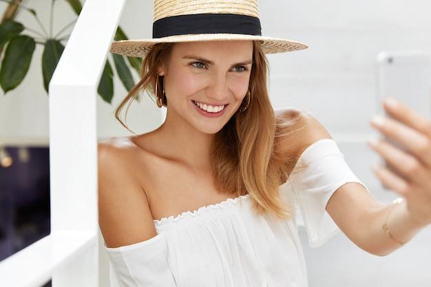 Feliz jovem turista feminina recriar no país quente, faz selfie no celular. mulher blogueira usa chapéu de verão e blusa faz tradução online e conta algo para os seguidores Foto gratuita