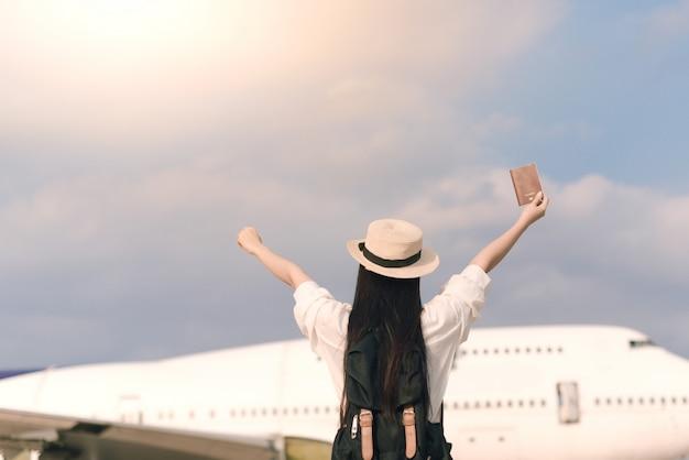 Feliz jovem turista no aeroporto com um passaporte para pegar um avião. liberdade e conceito de estilo de vida ativo Foto Premium