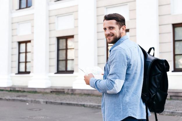 Feliz, jovem, viajante, homem, segurando, mapa, e, olhando câmera Foto gratuita