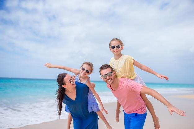 Feliz linda família de quatro na praia Foto Premium