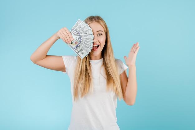 Feliz loira jovem com dinheiro dólar na mão isolada sobre azul Foto Premium