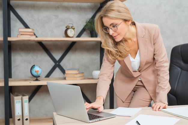 Feliz loira jovem empresária digitando no laptop no local de trabalho no escritório Foto gratuita