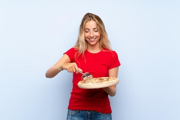 Feliz loira jovem segurando uma pizza sobre parede azul isolada Foto Premium