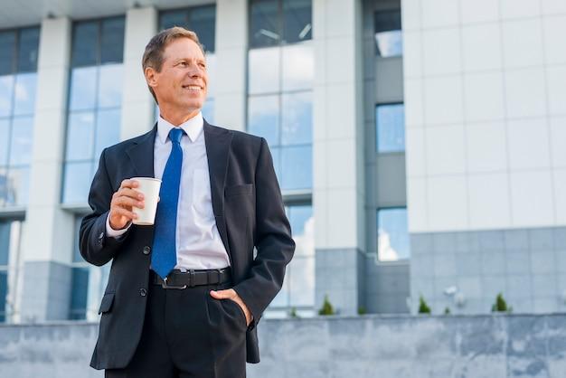 Feliz, maduras, homem negócios, com, xícara café, frente, predios Foto gratuita