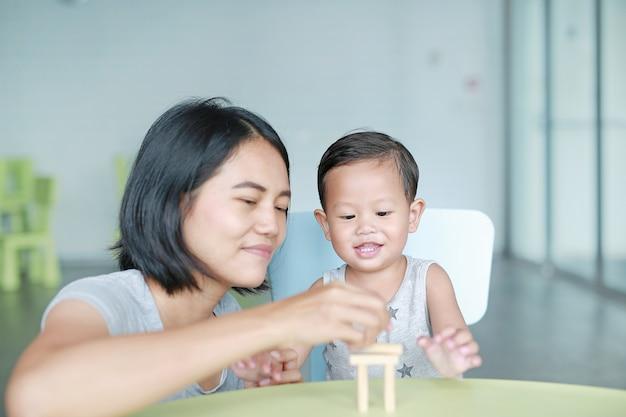 Feliz mãe asiática e bebezinho jogando blocos de madeira torre jogo para cérebro e habilidade de desenvolvimento físico em sala de aula. concentre-se no rosto de crianças. aprendizagem infantil e conceito de habilidades mentais. Foto Premium