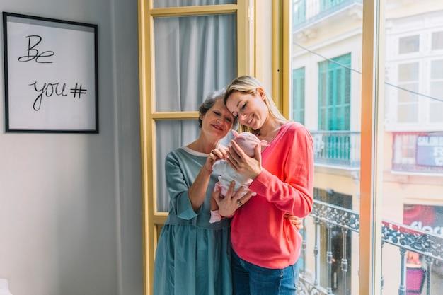 Feliz mãe e avó olhando para o bebê Foto gratuita