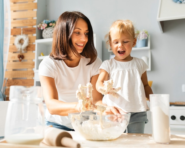 Feliz mãe e filha a preparar massa Foto gratuita