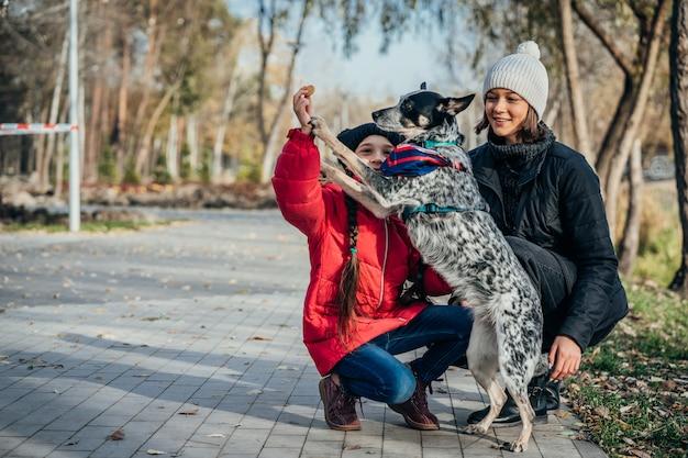 Feliz mãe e filha brincando com cachorro no parque outono Foto gratuita