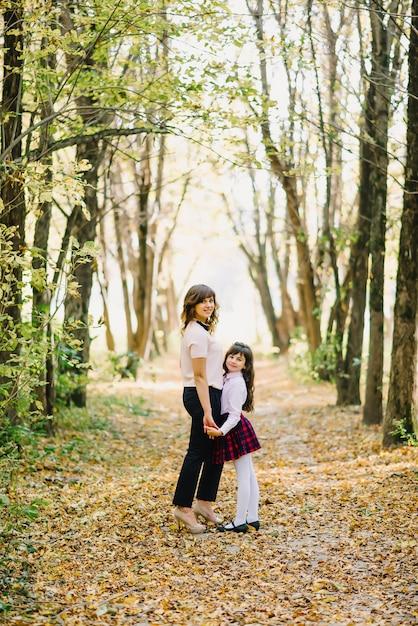 Feliz, mãe e filha caem no parque de mãos dadas e a sorrir Foto Premium
