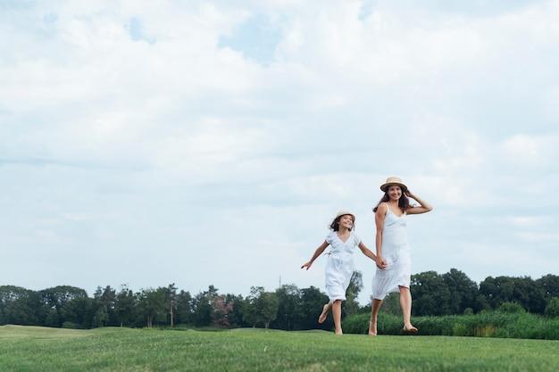 Feliz mãe e filha caminhando ao ar livre Foto gratuita
