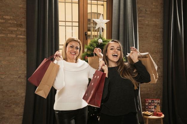 Feliz mãe e filha com sacos de compras Foto gratuita