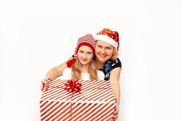 Feliz mãe e filha em chapéus vermelhos de papai noel, segurando um grande presente de natal em uma caixa com uma fita e um laço que eles dão. Foto Premium