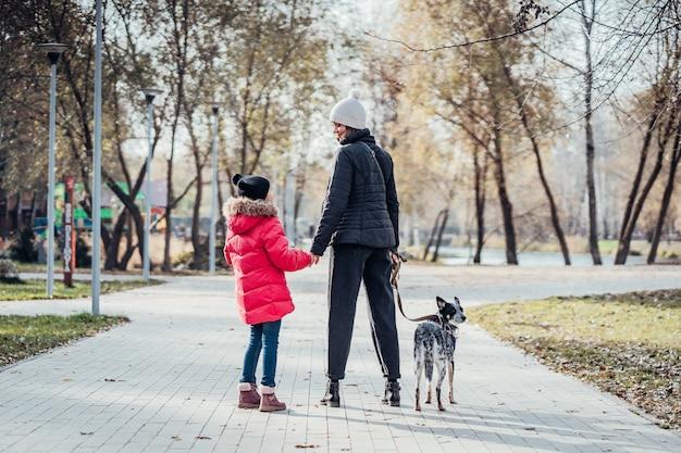 Feliz mãe e filha passear com cachorro no parque outono Foto gratuita