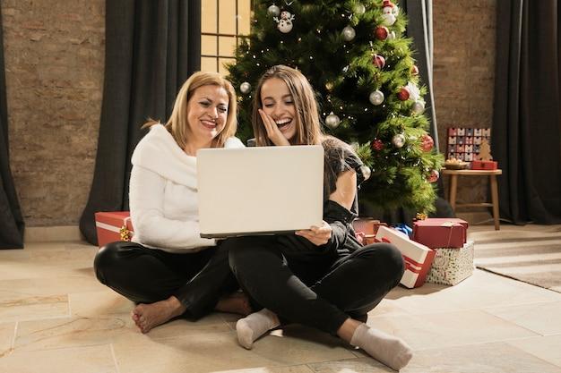 Feliz mãe e filha segurando um laptop Foto gratuita