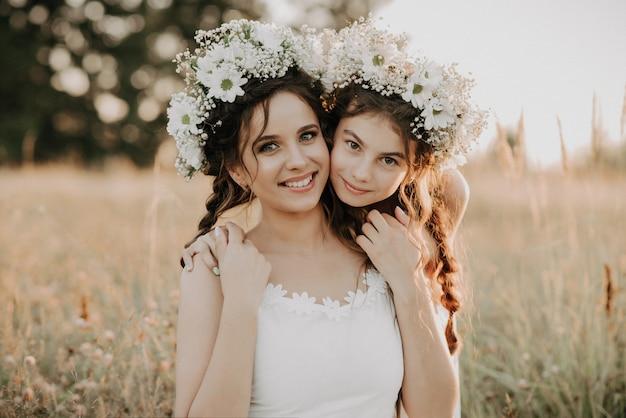 Feliz mãe e filha sorrindo e abraçando na grama no campo no verão Foto Premium