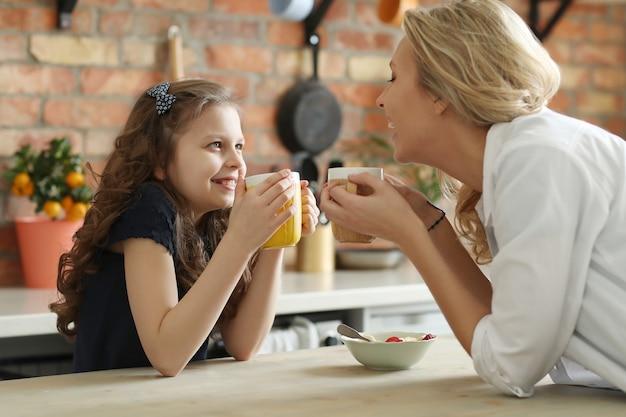 Feliz mãe e filha tomando café na cozinha Foto gratuita