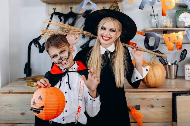 Feliz mãe e filho em pé no vestido extravagante, segurando pumpking e vassoura Foto Premium
