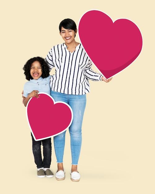 Feliz mãe e filho segurando ícones de coração Foto Premium